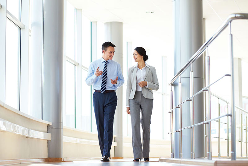 Man and woman walking down a white office hallway